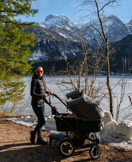 Side view of woman standing with baby stroller by lake during winter
