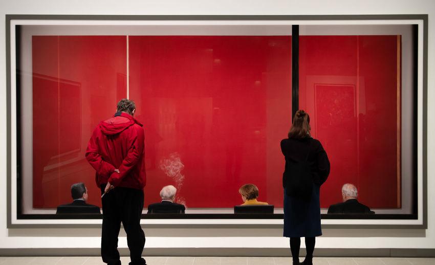 Rear view of people walking on red door