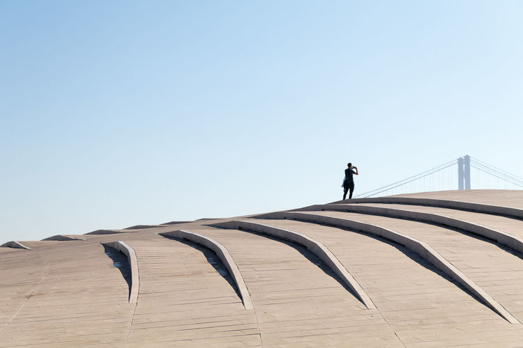 Low angle view of person walking against clear sky