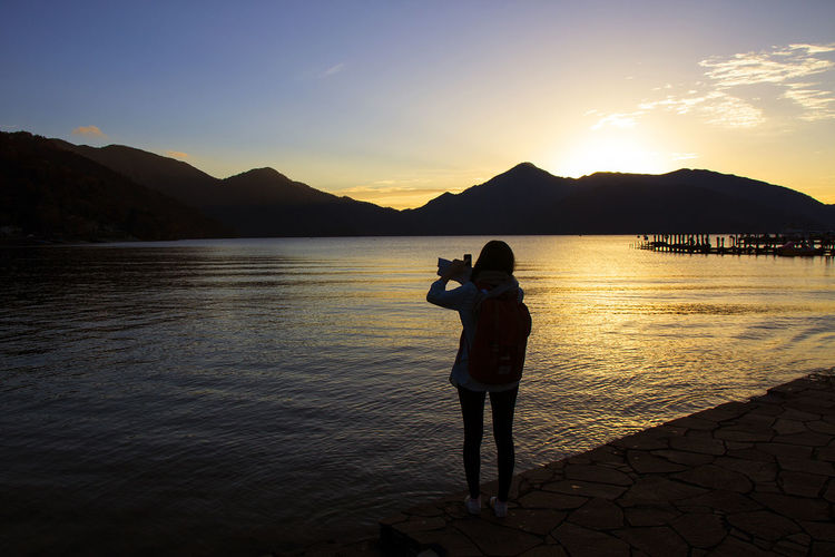 Beauty In Nature Blue Camera - Photographic Equipment Full Length Holding Lake Landscape Mobile Phone Mountain Nature One Man Only One Person Outdoors People Photo Messaging Photographing Photography Themes Portable Information Device Scenics Selfie Silhouette Smart Phone Sunset Technology Wireless Technology