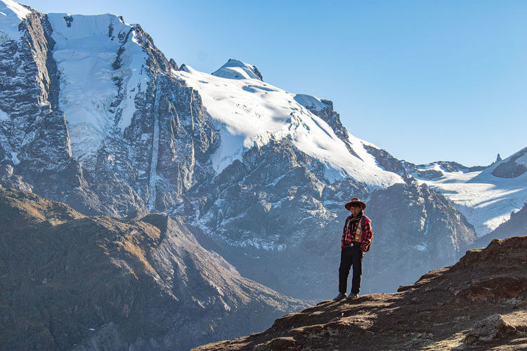 Full length of man standing on snowcapped mountain against sky