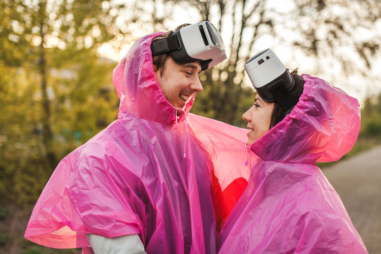 Happy young couple wearing raincoat and virtual reality simulator at park