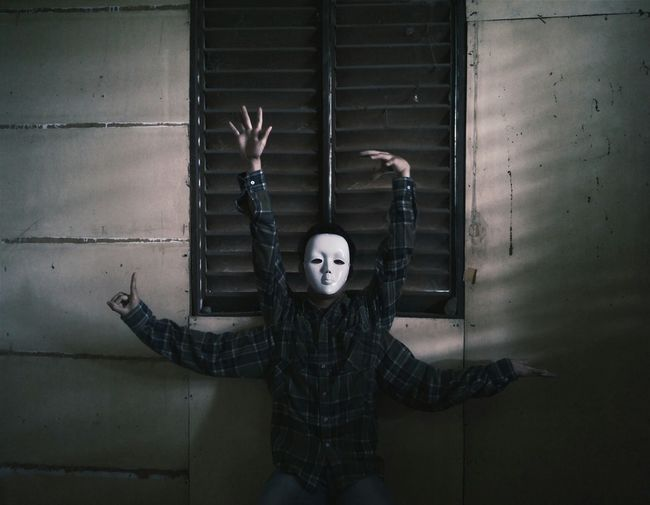 Man Wearing Mask With Artificial Hands Performing Dance Against Window