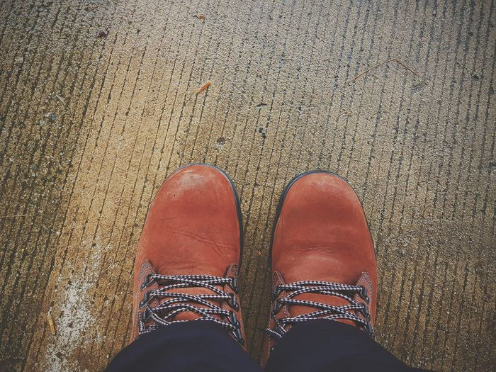 Low section of man wearing orange shoes on road