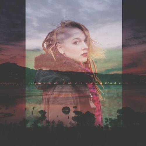 Portrait of beautiful woman against sunset sky