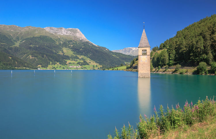 Campanile di Curon Water Mountain Architecture Built Structure Sky Blue Beauty In Nature Plant No People Nature Lake Clear Sky Day Building Exterior Place Of Worship Tower Scenics - Nature Building Outdoors Resia Resia Lake Reschensee Campanile Lago Lago Di Resia (Reschensee)