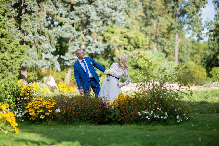 Bridal couple posing amidst plants at park