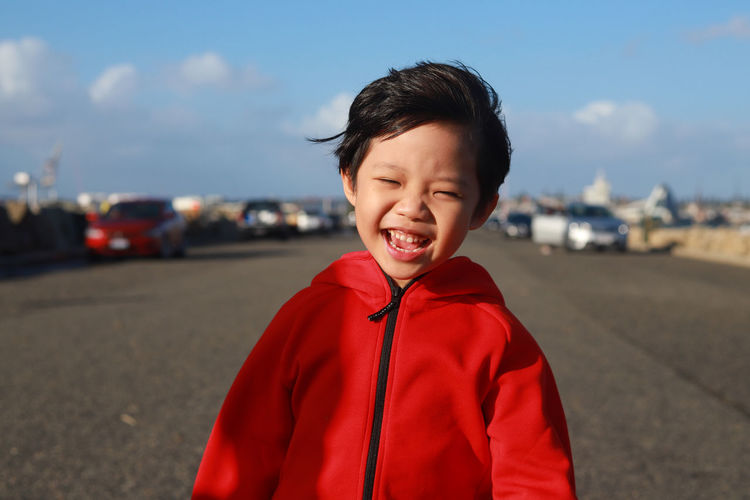 Portrait Of Boy Smiling While Standing On Road Against Sky