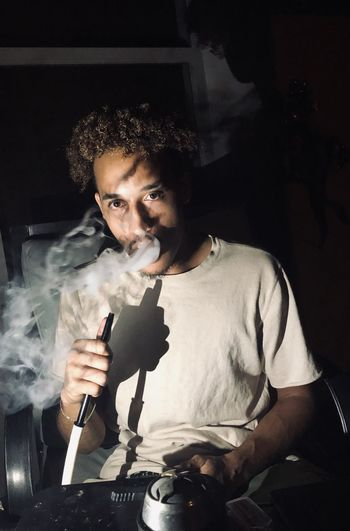 Portrait of young man smoking hookah at home