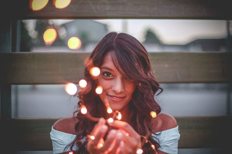 Portrait Of Young Woman Holding Illuminated String Light