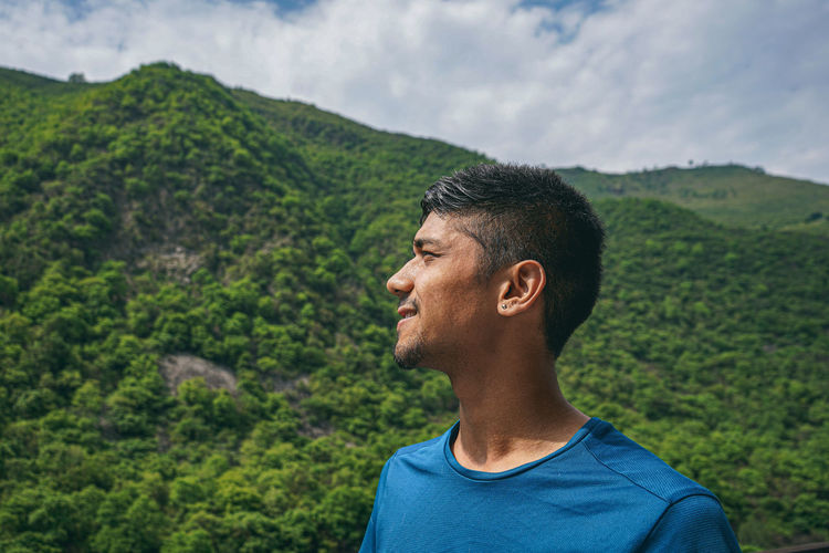 Portrait of young man looking away against mountains