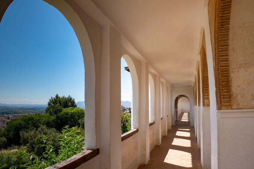 Alhambra (Granada) Alhambra De Granada  Granada Granada, Spain Alhambra Arcade Arch Architectural Column Architecture Building Built Structure Ceiling Colonnade Corridor Day Direction History Indoors  Nature No People Plant Sky Sunlight The Past The Way Forward Tree Window