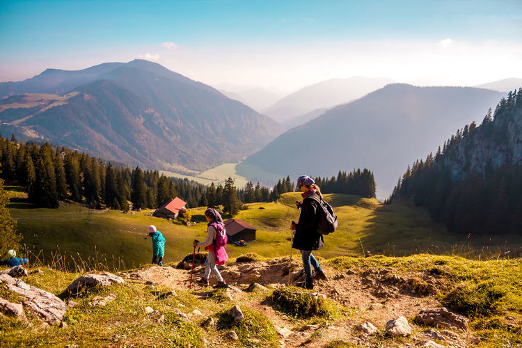Family hiking on mountain against sky during sunny day