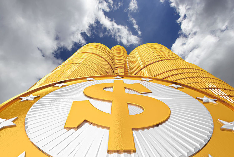 Stack Of Gold Coins Against Cloudy Sky