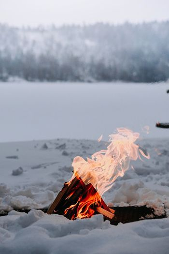 Tilt image of fire on land against sky during winter