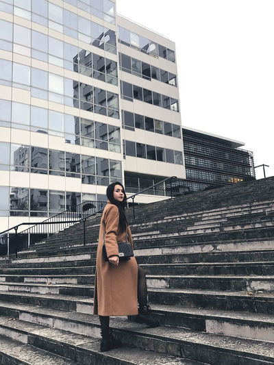 Woman sitting on staircase in city against sky