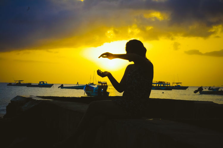 Silhouette woman gesturing while sitting pier against lake during sunset