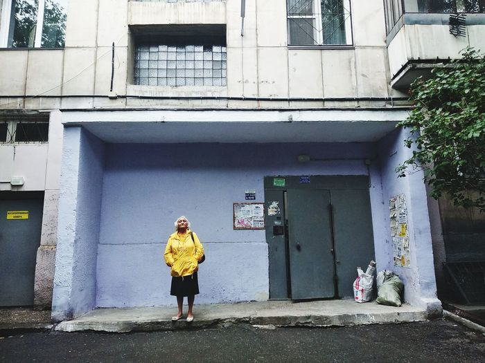 Full length of woman standing against building