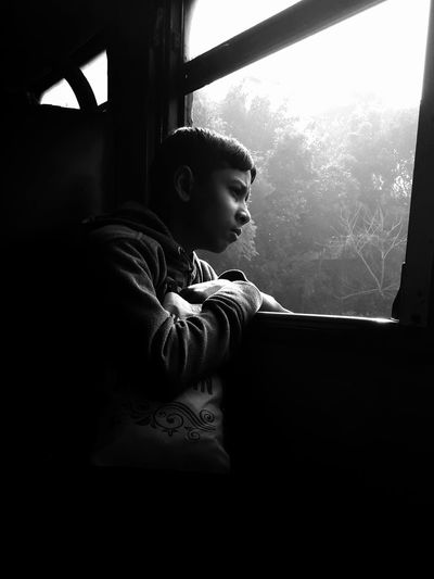Side View Of Boy Looking Through Window At Home