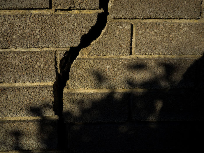 The crack in the wall Brick Wall Bricks Crack Crack Shadow Crack Wall No People Sunset Crack The Crack Wall Wall Cracks