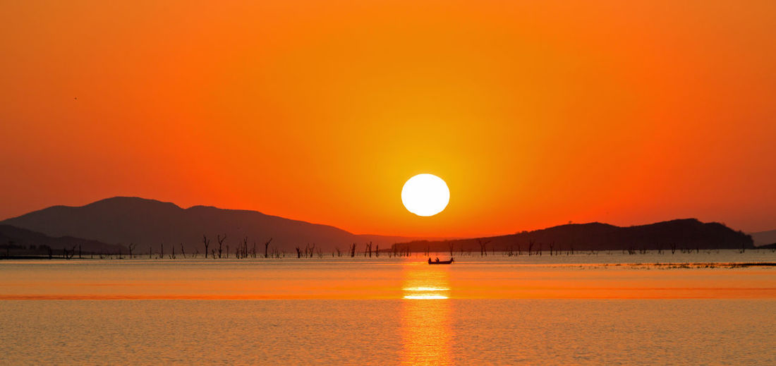 Beauty In Nature Full Moon Lake Kariba Landscape Nature No People Orange Color Outdoors Scenics Silhouette Sun Sunset Tranquility Water Zimbabwe Finding New Frontiers Miles Away
