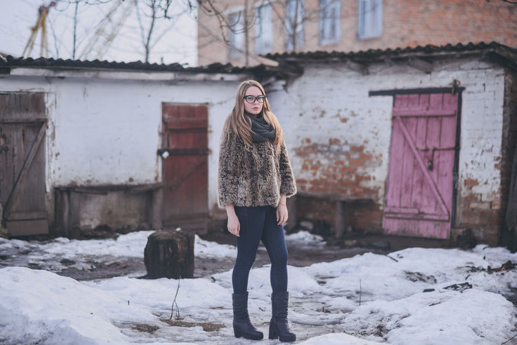 Full length portrait of woman standing on snow
