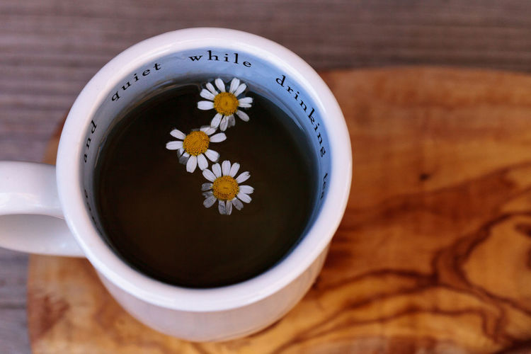 High angle view of chamomile tea with daisies in cup on cutting board