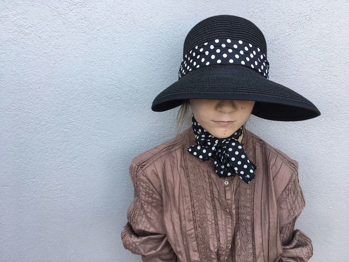 Young girl with hat against a grey wall. Hat Fashion One Person Black Color Headshot Standing Sun Hat Portrait People Girl Childhood Grey Color Grey Faded Loneliness Alone Solitude Lonely Polka Dots  The Week On EyeEm Mix Yourself A Good Time Fashion Stories