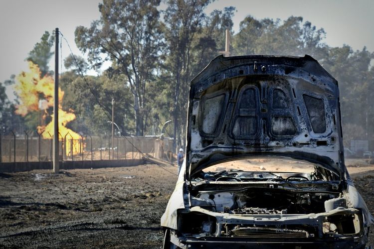 Damaged and burned car with open hood on dirt road