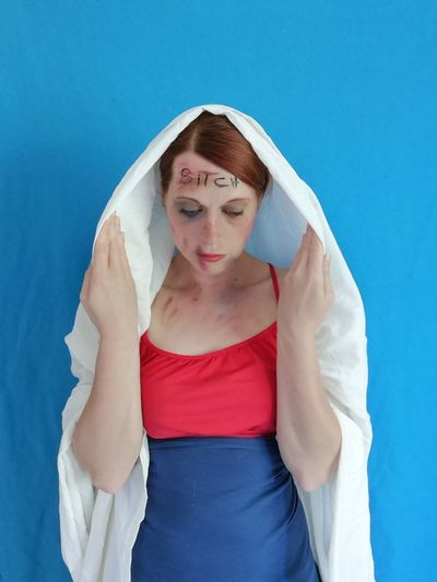 Thoughtful woman with wounds standing against blue wall