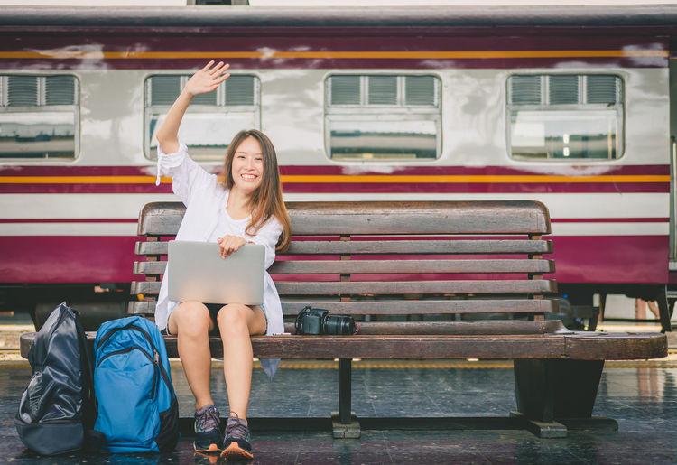 Full length portrait of woman sitting on seat