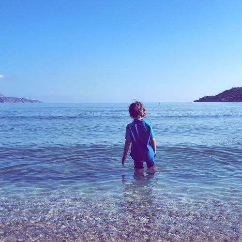 Boy on beach against clear sky