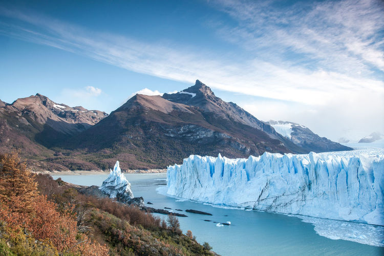 View to glacier perito moreno in argentina with the mountains in the back and colorful trees at fall