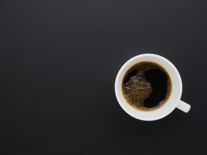 Directly above shot of coffee cup against black background