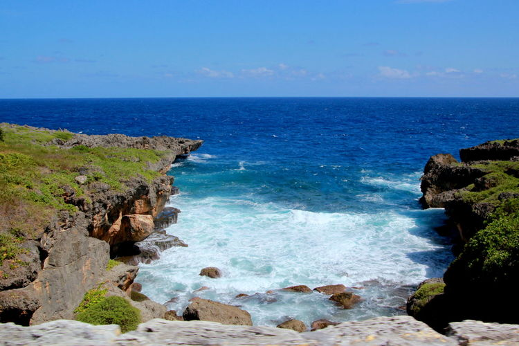 Water flows in a gap between the cliffs in Saipan facing the Pacific Ocean. Saipan Pacific Ocean Sea Water Scenics - Nature Rock Beauty In Nature Horizon Rock - Object Horizon Over Water Solid Tranquil Scene Sky Tranquility Land Nature Beach Idyllic Blue Rock Formation No People Outdoors Rocky Coastline