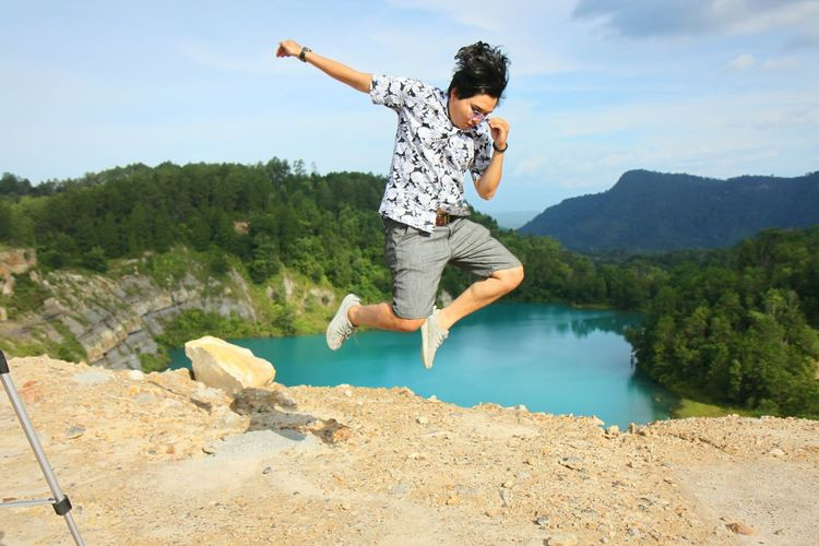 Full length of young man jumping on mountain