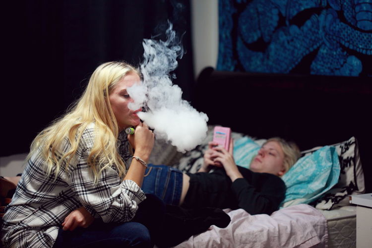 Woman exhaling smoke by sister on bed at home