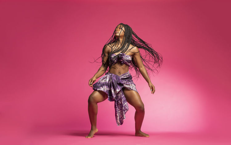 Beautiful African Black girl wearing traditional colorful African outfit does a dramatic dance move against a colorful pink background African African Traditions Adult African Dancer African Woman  Beautiful Woman Beauty Clothing Colored Background Dandelion Fashion Fashion Model Hair Hairstyle Human Hair Indoors  Lingerie Long Hair One Person Pink Background Pink Color Portrait Studio Shot Tradition Dress Women Young Adult Young Women