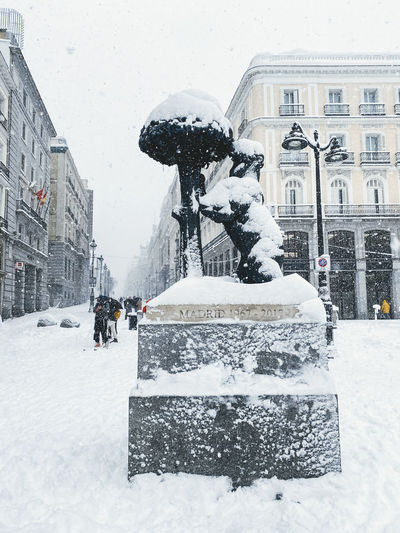 Statue on snow covered street against buildings in city