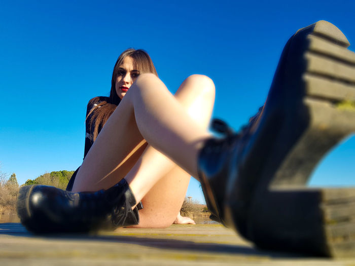 Surface Level Portrait Of Young Woman Sitting Against Clear Blue Sky