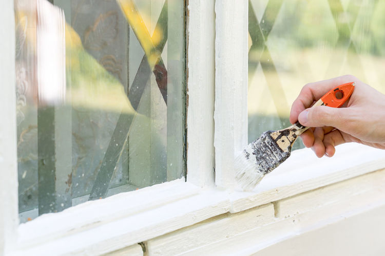 Cropped hand of person painting window sill