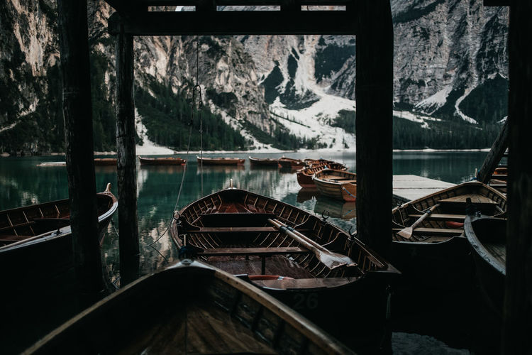 Boats Moored In Lake Against Mountains During Winter