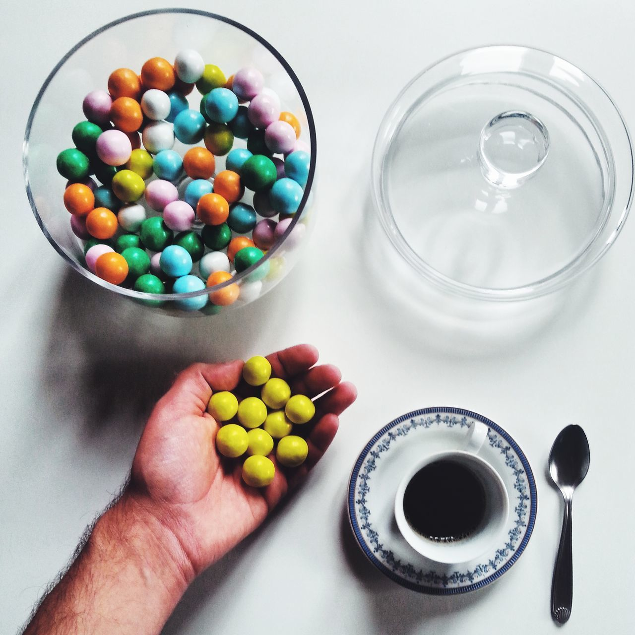 Cropped image of man with gumballs and black coffee on table at home