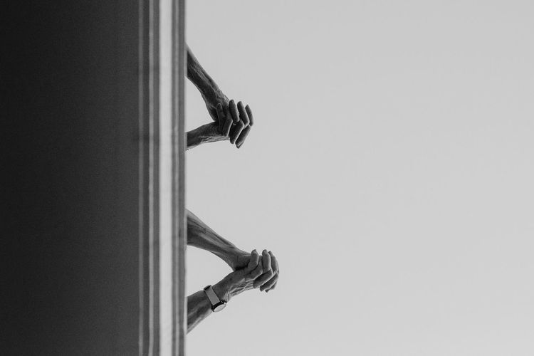 Cropped Image Of Hands Clasped Against Clear Sky