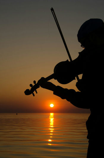 music on the pier. Fiddle Sunset Sunset_collection Nikonphotography Silhouette Water_collection Atthebeach Nikon D7000 Grand Bend, Ontario Nikon Life Musician Canada Coast To Coast Ontario, Canada Pattern, Texture, Shape And Form Light And Shadow EyeEm Best Shots - Nature Musical Instrument Taking Photos Shadows No Edit No Filter