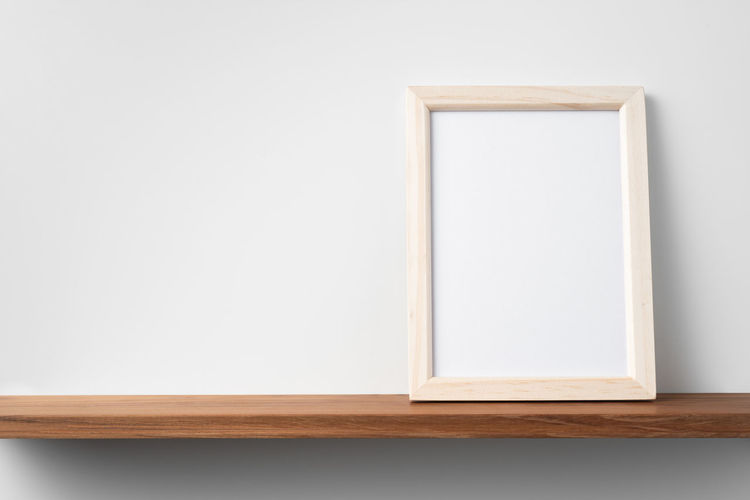 Close-up of white table against wall