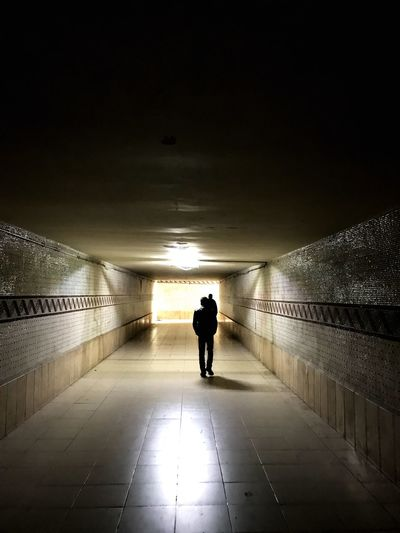 Rear view of silhouette man standing in illuminated tunnel