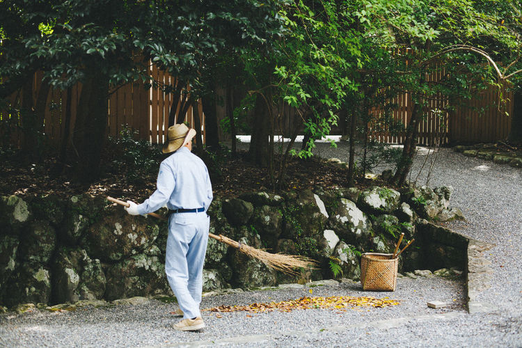 Rear view of man sweeping on footpath