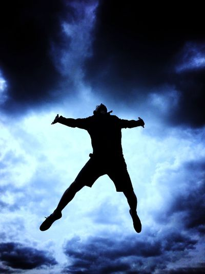 The silhouette of a man jumping high in the air as if possessed with his arms and legs spread wide and a dramatic electric blue sky behind. Low Angle View Silhouette Sky Mid-air Cloud - Sky Full Length Energetic Men One Person Outdoors Jumping Real People Leap Leap Of Faith Jump Free Freedom Possessed Dramatic Blue Electric Man Free Spirit Pain High The Week On EyeEm Lost In The Landscape Rethink Things