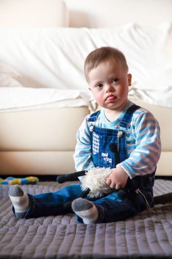 Babyboy Baby Babyhood Bed Casual Clothing Child Childhood Cute Domestic Room Down Syndrome Front View Full Length Furniture Home Interior Indoors  Innocence Mental Health  One Person Real People Sitting Sofa
